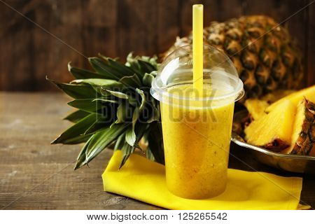 Pineapple smoothie in plastic cup on wooden background
