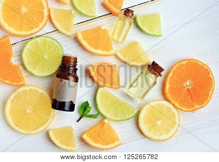 Citrus essential oil. Various citrus fruit and aroma bottles. Orange, lime, lemon slices. Top view.
