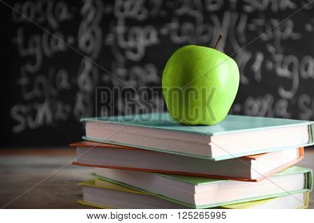 Few books with green apple on table