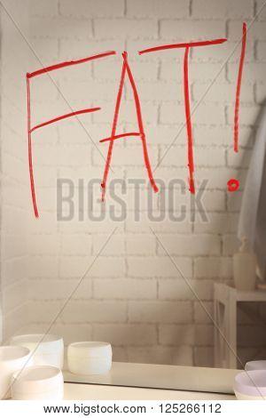 Word FAT written on mirror in the bathroom