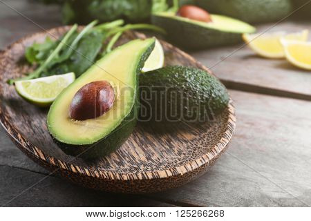 Sliced avocado with lime, spinach and arugula on wooden plate