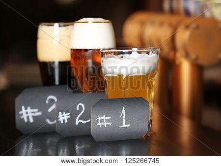 Three sampling glasses of beer in a bar