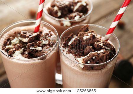 Glasses of chocolate milkshake on wooden table closeup