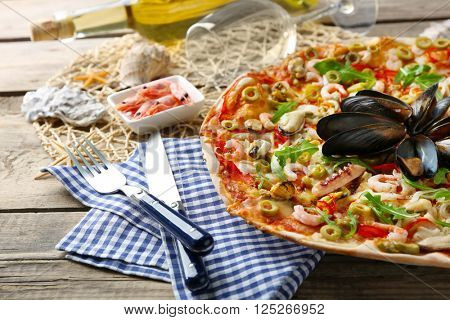 Pizza with seafood, red pepper, green olives and bottle of wine on wooden table