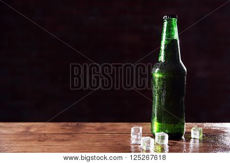 Green glass bottle of beer and ice cubes on dark background, close up