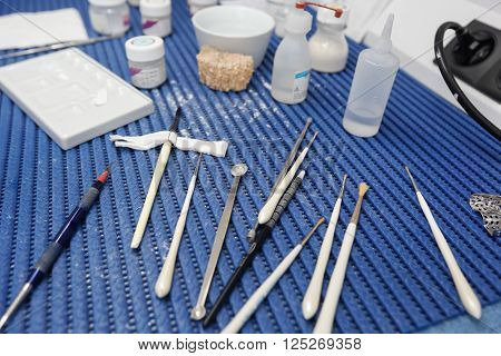Dental lab tools and instruments for porcelain layering in the process of denture veneer and implant manufacturing. Dentistry prostodontics prosthetics medical technology and equipment concept.