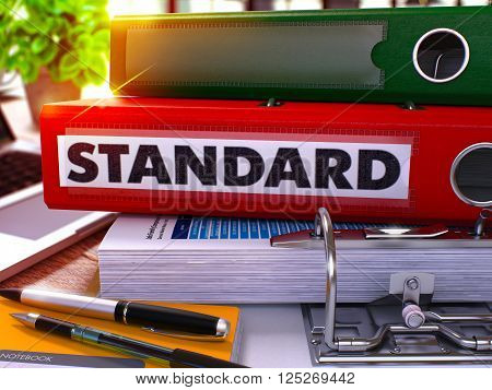 Standard - Red Office Folder on Background of Working Table with Stationery and Laptop. Standard Business Concept on Blurred Background. Standard Toned Image. 3D.