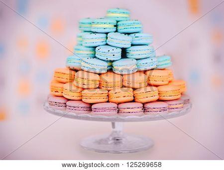 Many varicolored tasty macaroons on glass tray, close up