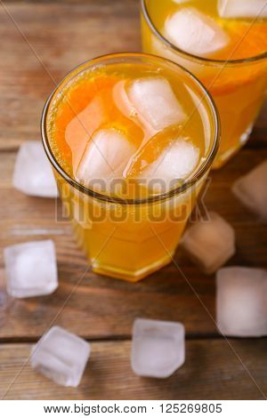 Glasses of orange juice with ice block on wooden background, close up