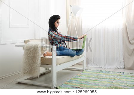 Young girl in computer glasses on a white sofa with laptop. Hipster freelancer woman works at home. Home office, freelance. Brunette with laptop in modern interior at white couch. Soft tone, high key.