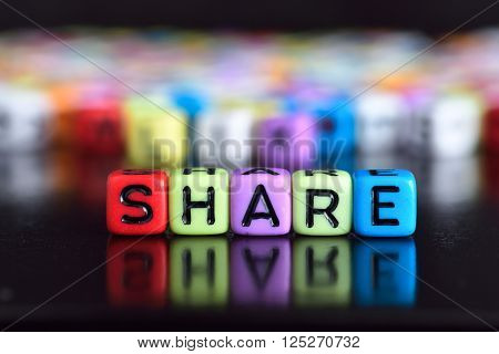 Colorful cube with word Share on wooden table Share on wooden table