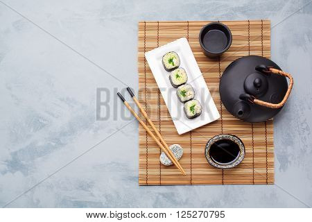 Japanese Cuisine Teapot green tea sushi and soy sauce. Food background with copyspace