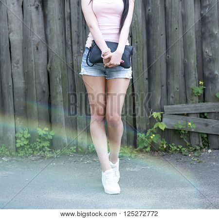 Fashionable girl holding bag posing in white sneakers, opposite the wooden fence with pink nail polish and bright glare from the sun