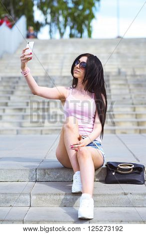 Girl sitting on the stairs, in the street makes your phone beautiful self, fashion style glamor sexy woman lying near leather bag