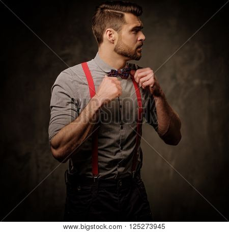 Young handsome man with beard wearing suspenders and bow tie, posing on dark background.