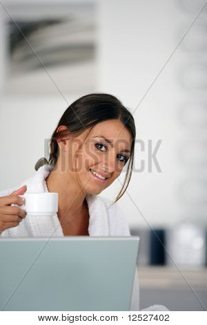 Portrait of a smiling woman wearing a bathrobe with a cup in front of a laptop computer