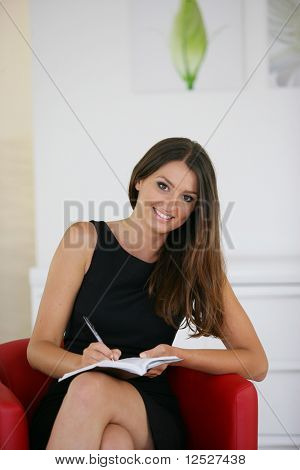 Portrait of a smiling woman sat on an armchair writing on a paper