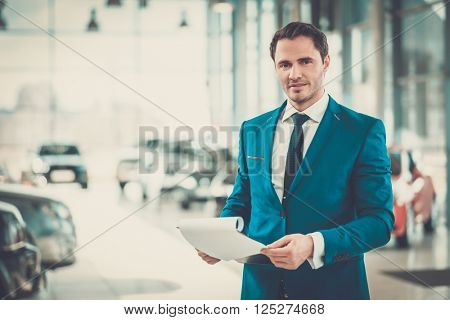 Confident young car dealer standing in showroom.