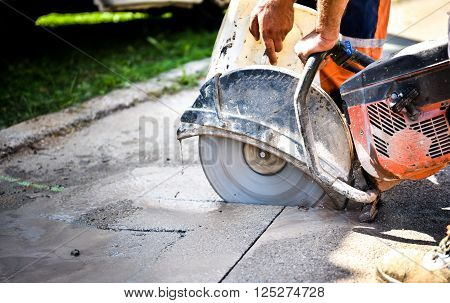 Construction Worker Cutting Asphalt Paving For Sidewalk