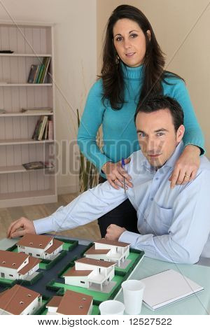 Couple in front of an architect model in an office