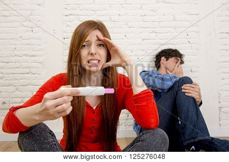 young couple worried with girl holding positive result pregnancy test and boyfriend sad and depressed