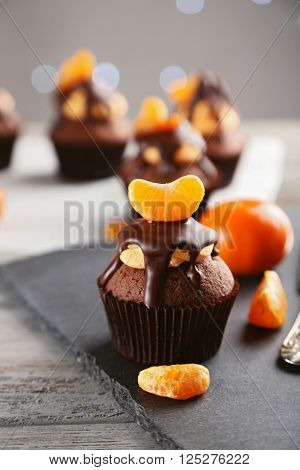 Tasty cupcake with fruits on slate plate over light wooden background