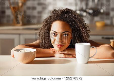 Have a substantial meal. Pleasant beautiful girl folding her hands and leaning on the table while having a meal