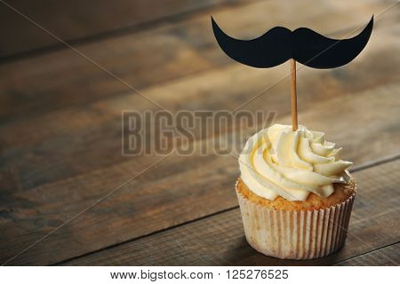 Delicious creative cupcake with mustache on wooden table