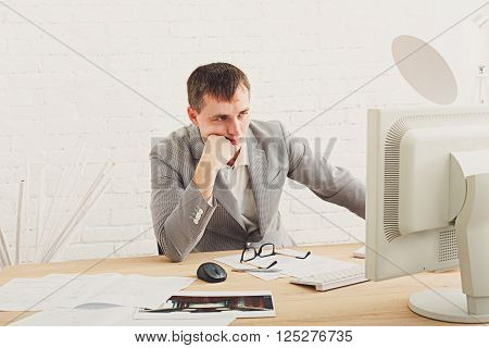 Young businessman working in white modern office interior, thoughtful, sitting at computer table. Office worker with eye glasses, job in internet. High key, soft tone. Business man in modern office.