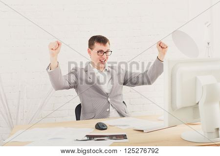 Winner businessman happy, succesful, in white modern office interior, sitting at computer table. Office worker in eye glasses, job in internet. High key, soft tone. Businessman win prize, gambling.