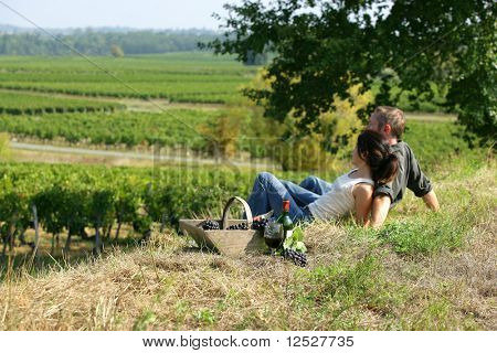 Couple sat on the grass in front of vineyards