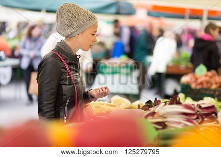 Woman buying fruits and vegetables at local food market. Market stall with variety of organic vegetable.