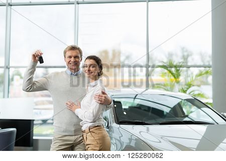 Young couple with car keys indoors