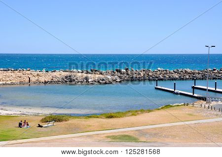 HILLARYS,WA,AUSTRALIA-JANUARY 22,2016: People picnicking on the foreshore of a cove with boat docks, groyne and the Indian Ocean waters in Hillarys, Western Australia.