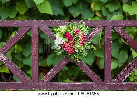 Wedding bouquet on garden benchl. Bride's traditional symbolic accessory. Floral composition with red celosia flowers.