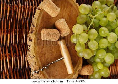 Wine corks and tailspin with bunch of grapes on wooden background