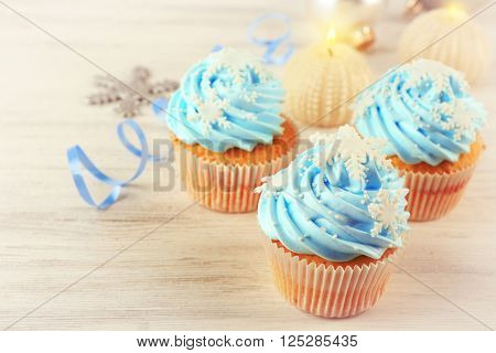 Few tasty blue cupcakes with decorations on light background