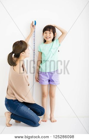mother measures the growth of her  daughter