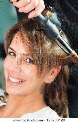 Curling hair in beauty salon, vertical image