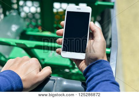 Closeup on person holding mobile smart phone in hand during shopping. Cellphone and cart on store goods background.