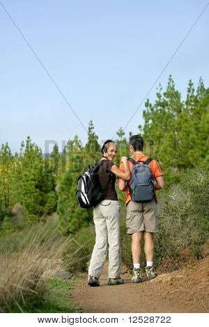 Young smiling woman with a man making some hike