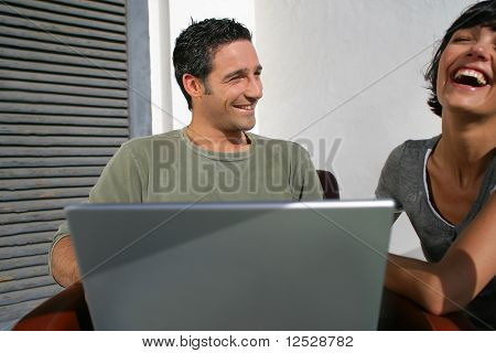 Happy couple laughing in front of a laptop computer
