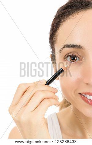 Woman using eyeliner. Isolated on white background.