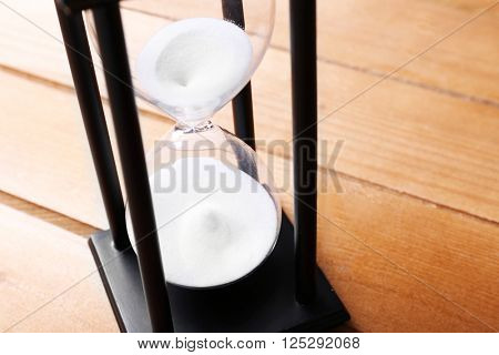 Black sand glass on wooden background, close up