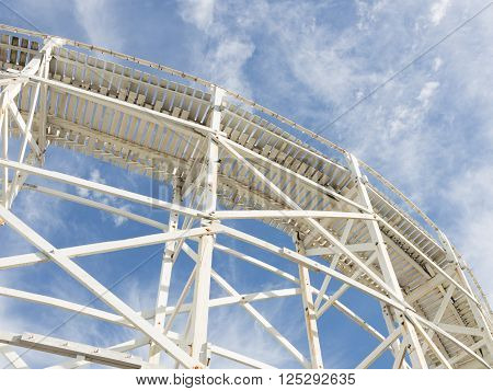beautiful abstraction of a white wooden structure of the old road on the background of blue sky with white cumulus and cirrus clouds