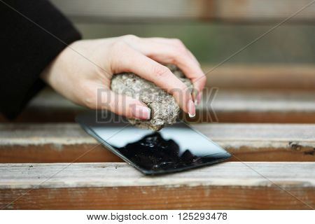 Female hand crushing with stone screen of mobile phone on wooden bench