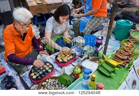 CHIANG MAI, THAILAND - FEB 20: Two women cooking food from quail eggs at big street fair with fast food court on February 20, 2016. Population of Lampang is near 59000 people