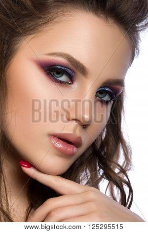 Close up portrait of young beautiful woman with purple evening make up touching her chin. Modern fashion smokey eyes makeup. Studio shot.