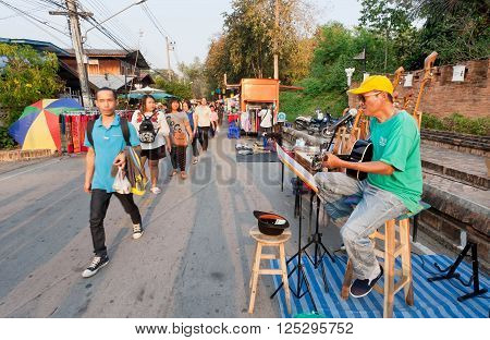 LAMPANG, THAILAND - FEB 19: People walking past a guitarist playing music on the street fair surrounded by musical instruments on February 19, 2016. Population of Lampang is near 59000 people
