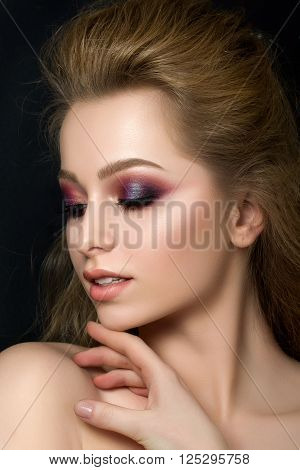 Close up portrait of young beautiful woman with purple evening make up over black background. Modern fashion smokey eyes makeup. Studio shot.
